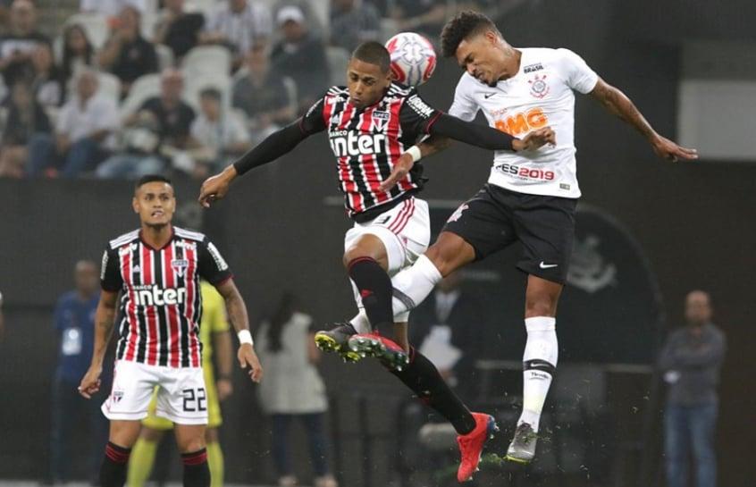 Everton, ao fundo, observa disputa de bola entre o zagueiro Bruno Alves e o volante Júnior Urso, do Corinthians